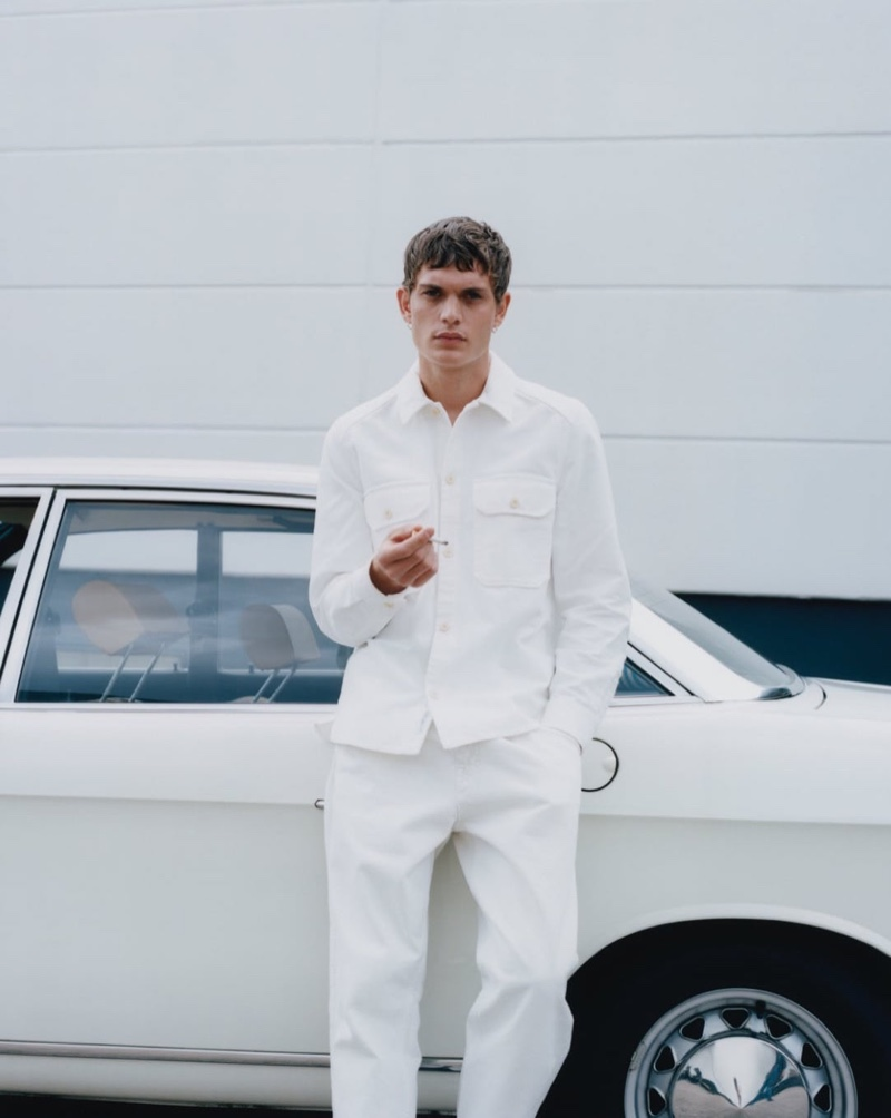Clad in white, Julien Pernot wears menswear from fashion brand Closed.