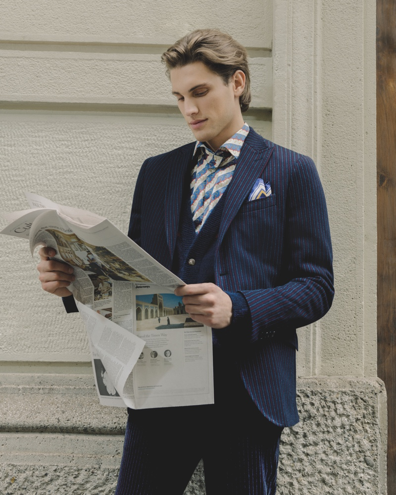 Reading the paper, Maxime Trabouile embraces professional style in an Etro 24 Hour jacket.
