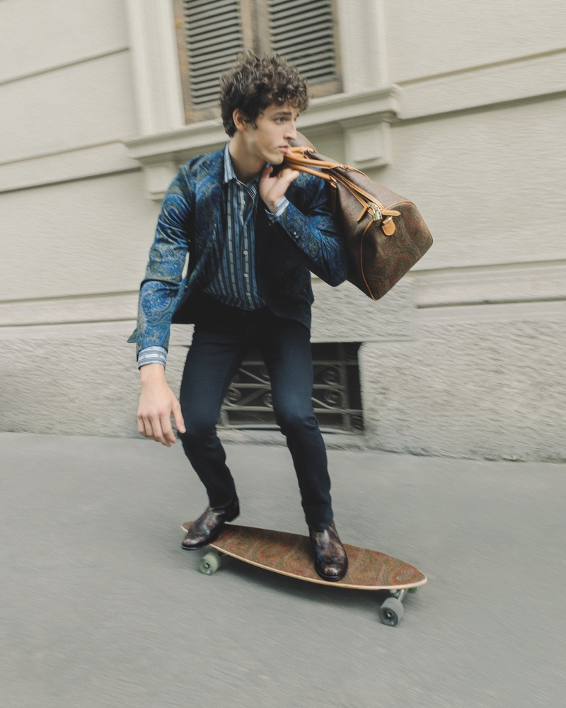 Skateboarding on an Etro longboard, Alberto Perazzolo models a paisley print 24 Hour jacket.