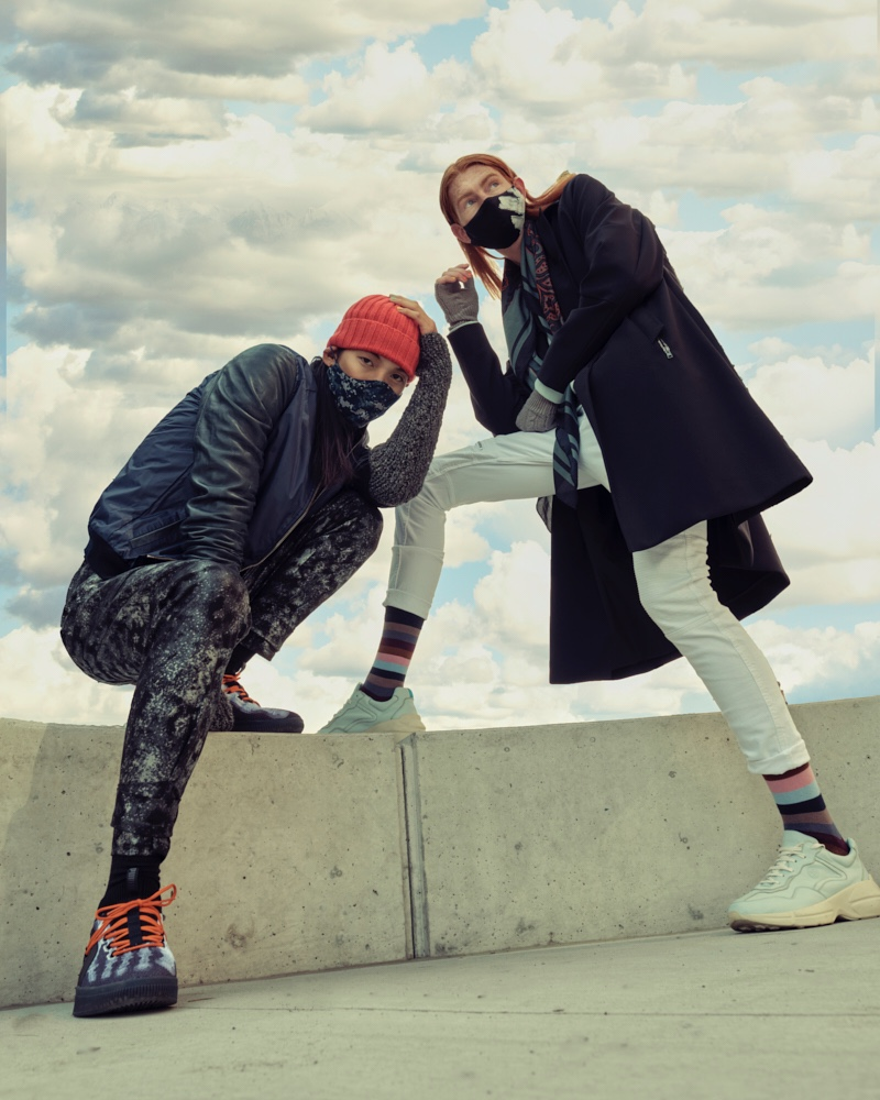 Left: Sooleen wears bomber Hip and Bone, beanie Leone Napoli, sneakers Puma, printed mask Mayer Man Custom, tank and pants House of Dwir. Right: Jayden wears hand warmers Aldo, socks Hudson's Bay, sneakers Hip and Bone, mask, Mayer Man Custom, pants and scarf H&M, sweater and trench Christopher Bates.