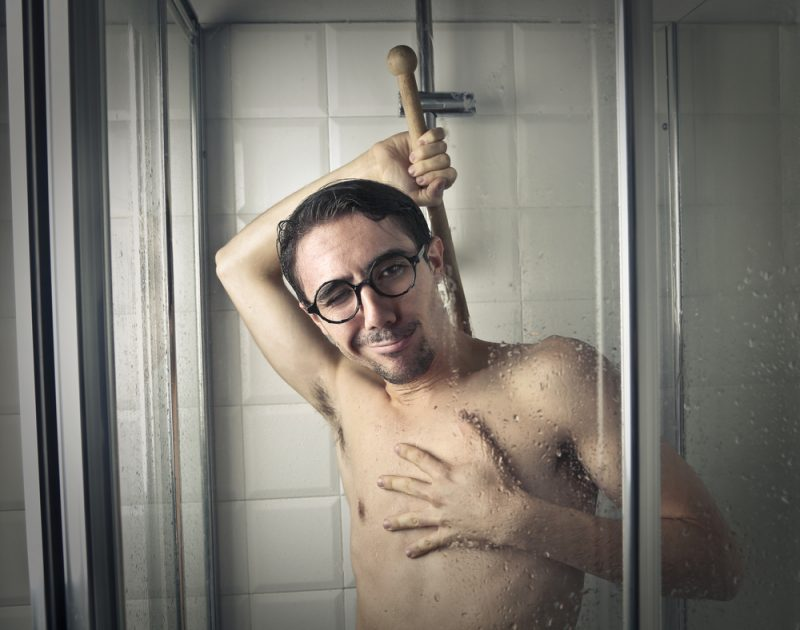 Man Using Cleaning Brush in Shower
