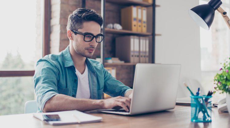 Man Wearing Glasses Working on Laptop