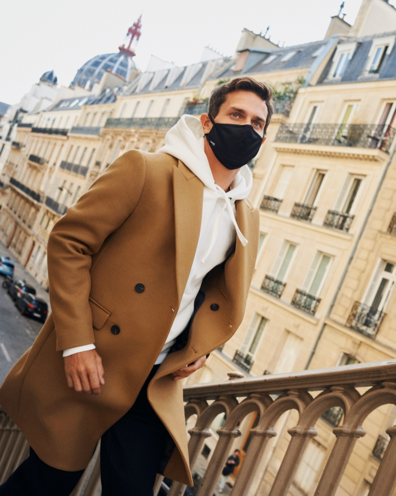 Vincent Lacrocq steps out in a face mask as he dons a hoodie and double-breasted coat from Mango's Comfy collection.