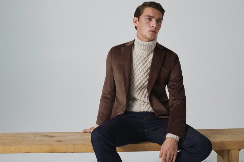 Otto Lotz dons a slim-fit dyed wool blazer with a cable-knit turtleneck sweater and jeans from Massimo Dutti.