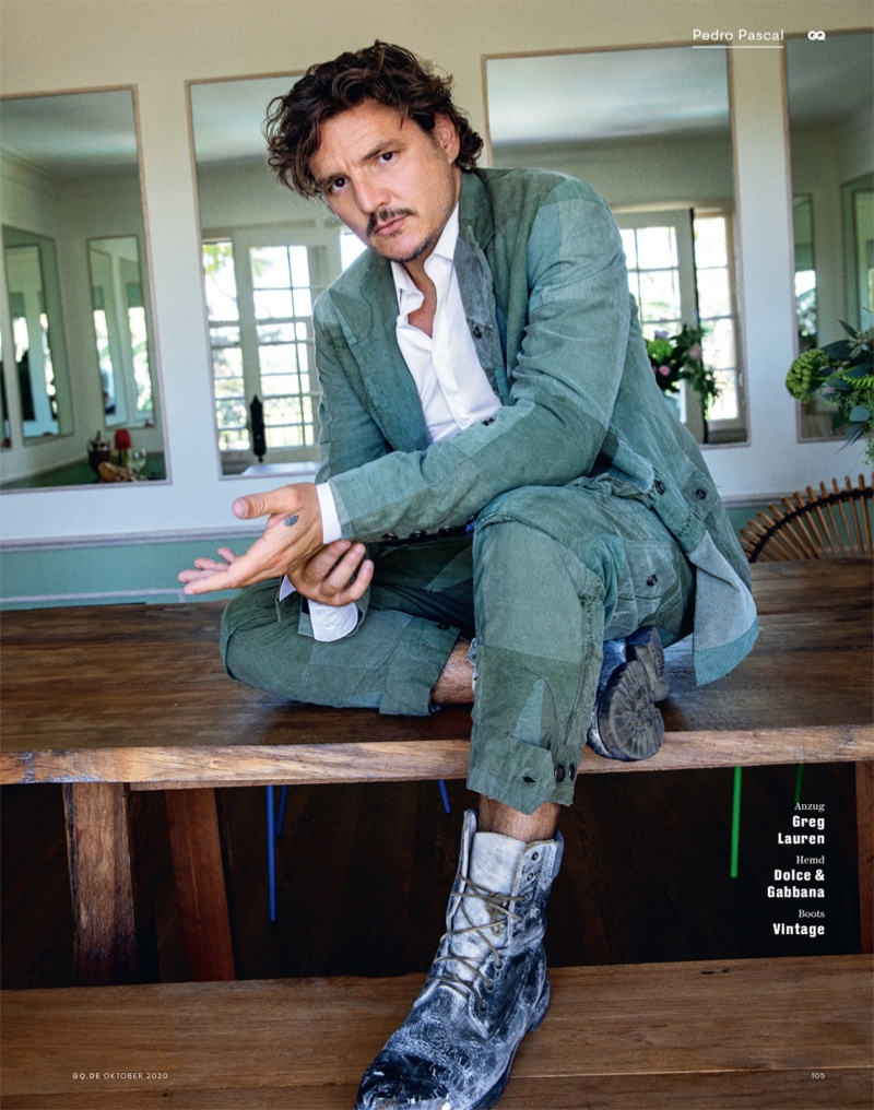 Appearing in a fashion shoot for GQ Germany, Pedro Pascal dons a patchwork suit by Greg Lauren. He also wears a Dolce & Gabbana shirt with vintage boots.