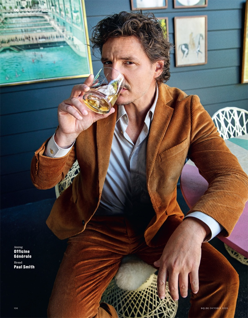 Enjoying a drink, Pedro Pascal sports a corduroy suit by Officine Générale. Photographed for GQ Germany, he also wears a Paul Smith shirt.