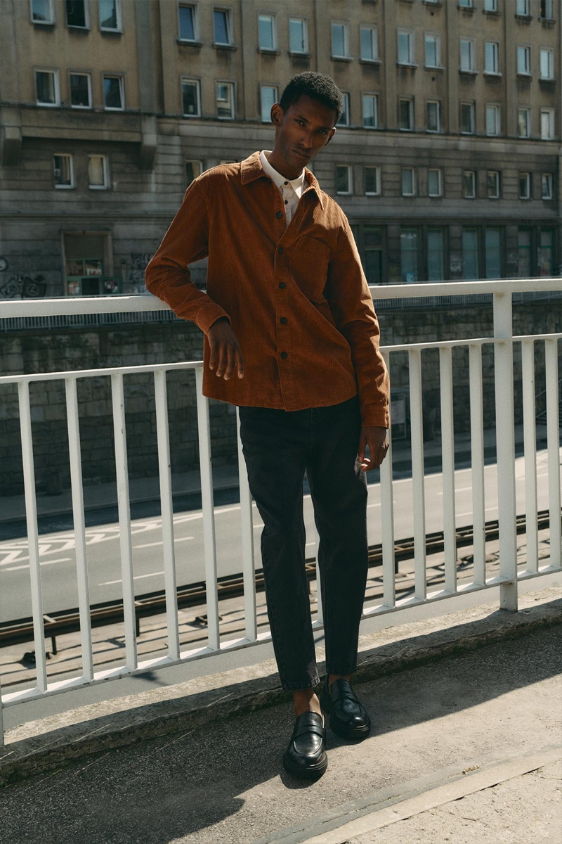 Sporting a corduroy overshirt and denim jeans, Myles Dominique embraces fall style from Reserved.