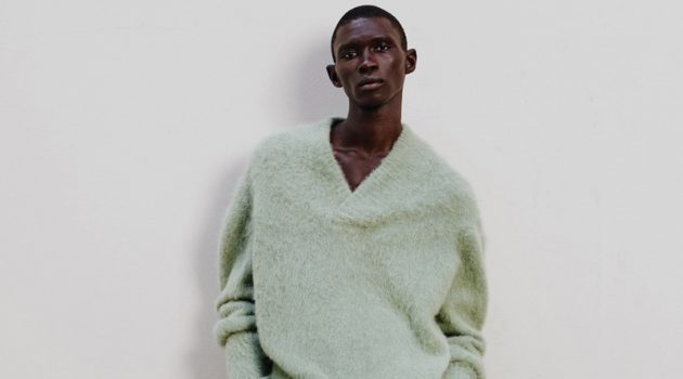 Mixing muted tones, Fernando Cabral stands out in a v-neck wool-mix sweater and corduroy trousers with chunky leather boots by COS.