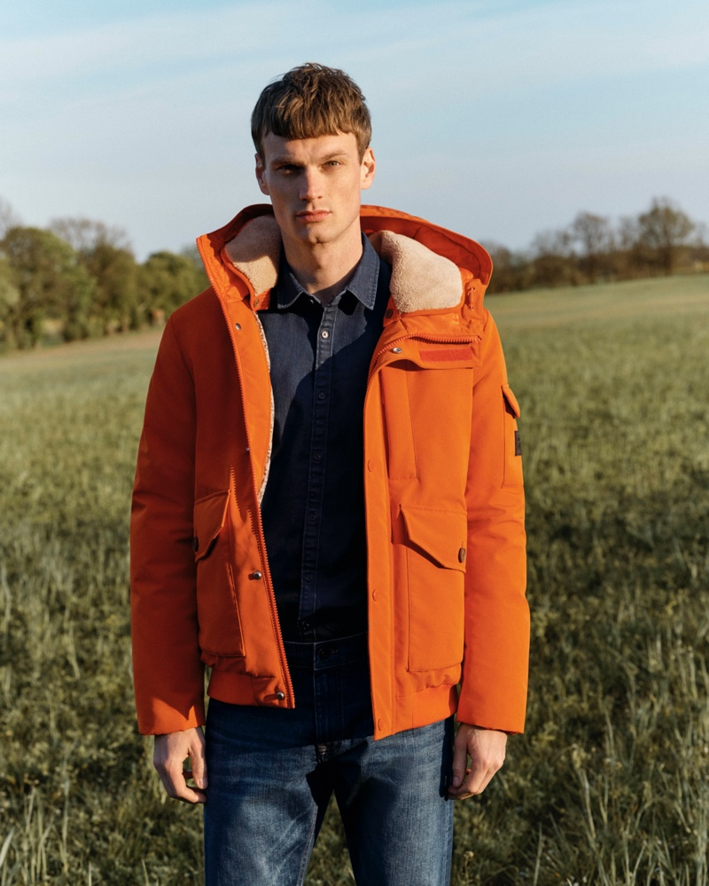 Max Bender rocks an orange hooded jacket for Esprit's fall-winter 2020 campaign.