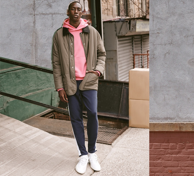 Pop of Color: East Dane suggests switching up the mundane with an easy pairing of comfortable basics and a splash of color. Front and center, model Macky Dabo dons an Adidas x Pharrell Williams Basics hoodie with POLO Ralph Lauren track pants, a Maison Margiela recycled nylon quilted jacket, and Adidas x Craig Green sneakers.