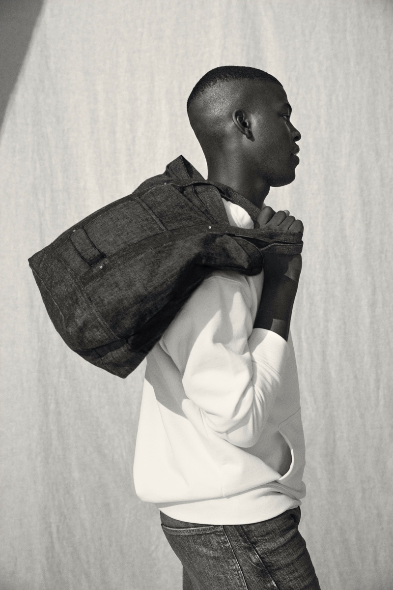 Connecting with H&M for fall, model Evandro Laurens takes hold of a denim tote from the brand's Jeans Redesign collection.