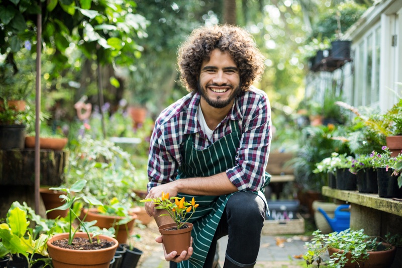 Happy Smiling Male Gardener Greenhouse Potted Plant