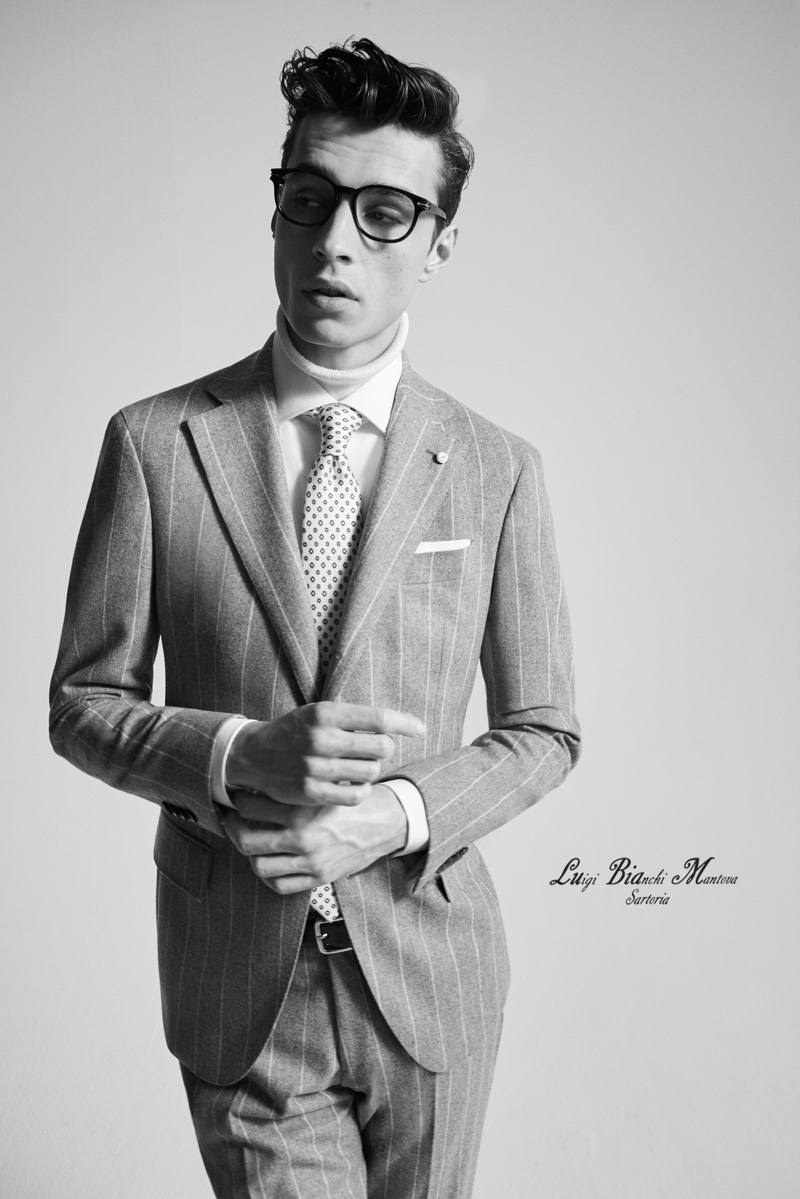 Charming in a pinstripe suit by Luigi Bianchi Mantova, Adrien Sahores finishes his look with a smart pair of black framed glasses.