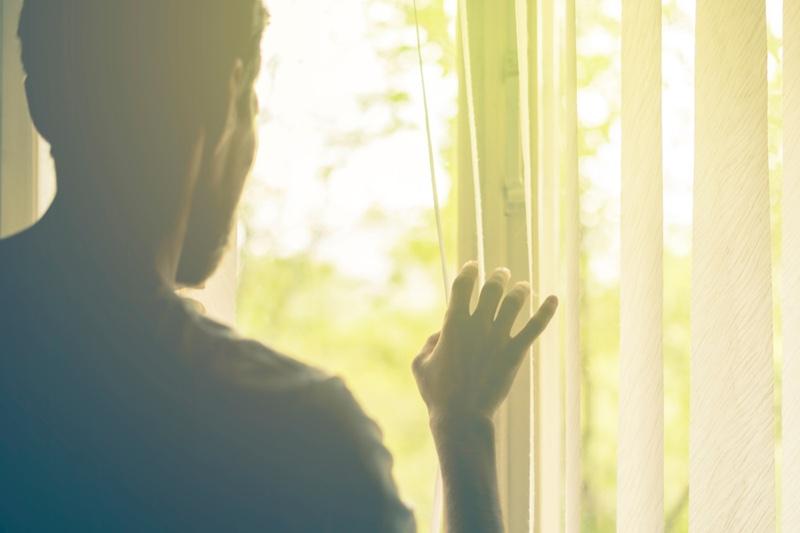 Man Looking Through Vertical Blinds Sun