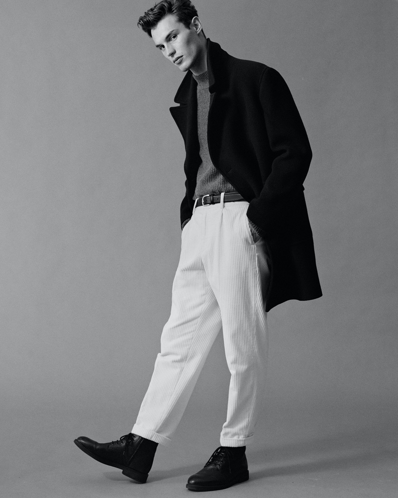 Appearing in a black and white photo, Kit Butler dons a textured fall look from Mango's Urban Essentials collection. Front and center, Kit wears a chic coat with a ribbed turtleneck sweater, corduroy pants, a leather belt and boots.