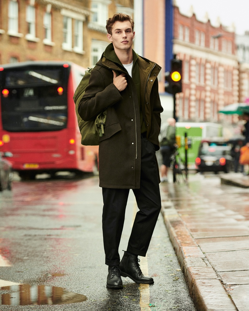 Taking to the wet city streets, Kit Butler makes a case for monochromatic style. Stopping for a photo, Kit wears a parka with a knit sweater, trousers, and leather boots from Mango's Urban Essentials collection.