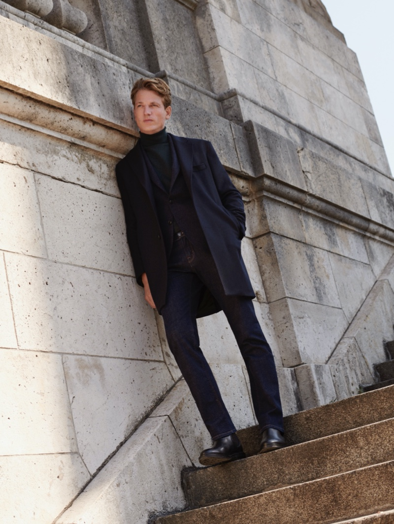 Layering for fall, Hugo Sauzay dons a sleek coat, suit jacket, turtleneck, and jeans from Massimo Dutti.