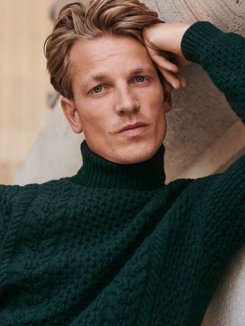 Front and center, Hugo Sauzay models a green cable-knit sweater from Massimo Dutti's fall-winter 2020 collection.