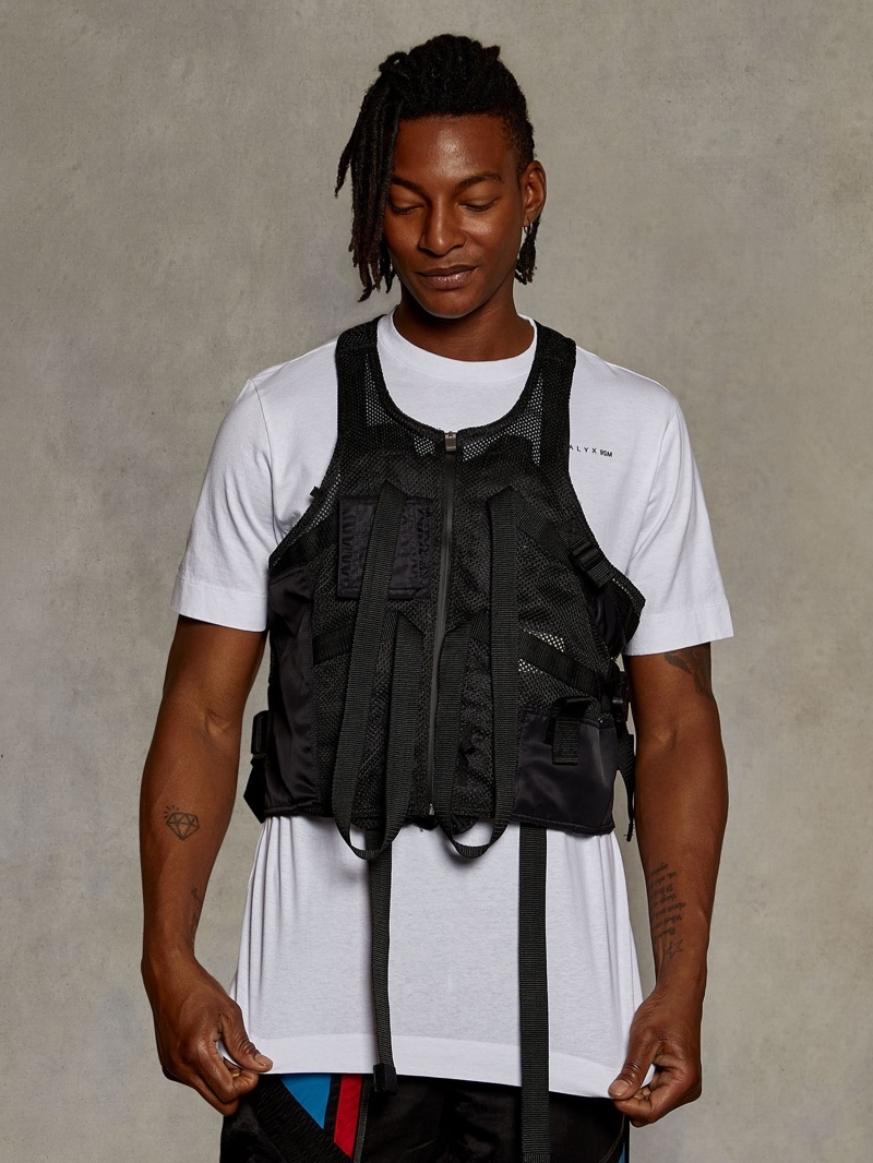 Tackling military-inspired style, Ty Ogunkoya models a 1017 ALYX 9SM t-shirt and vest with Feng Chen Wang trousers.