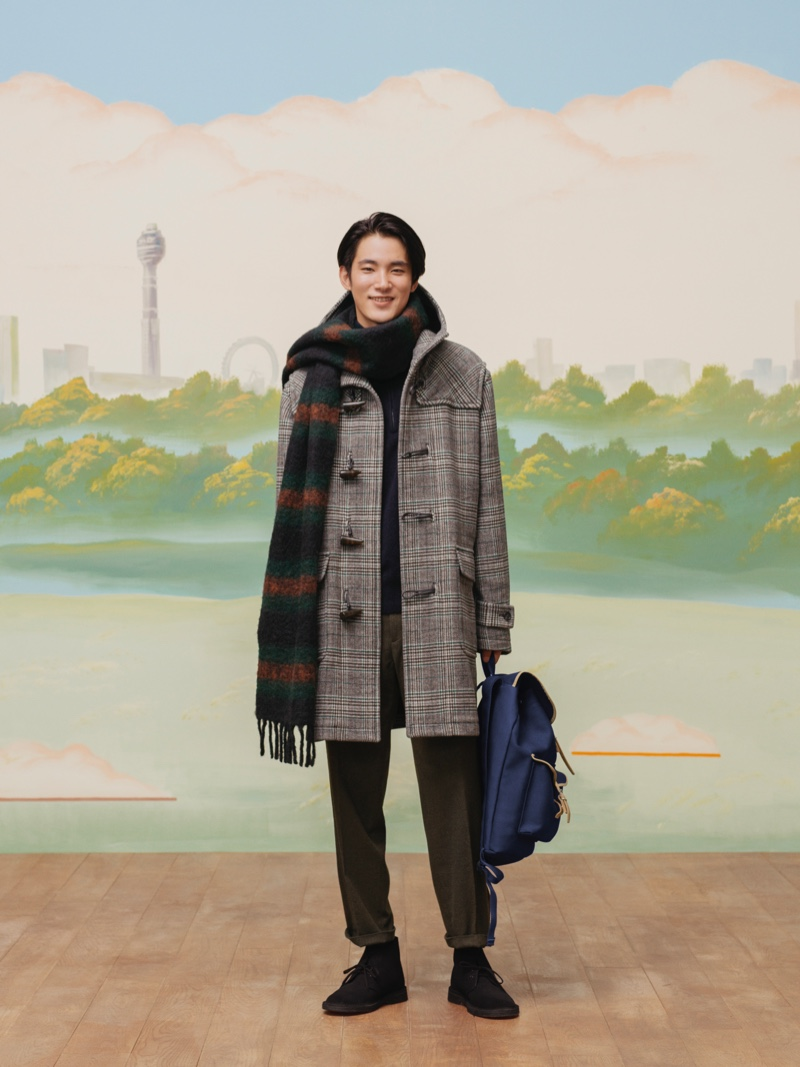 All smiles, model Hikaru Takakamo wears a checked duffle coat, pleated trousers, and a striped scarf from the UNIQLO x JW Anderson fall-winter 2020 collection.