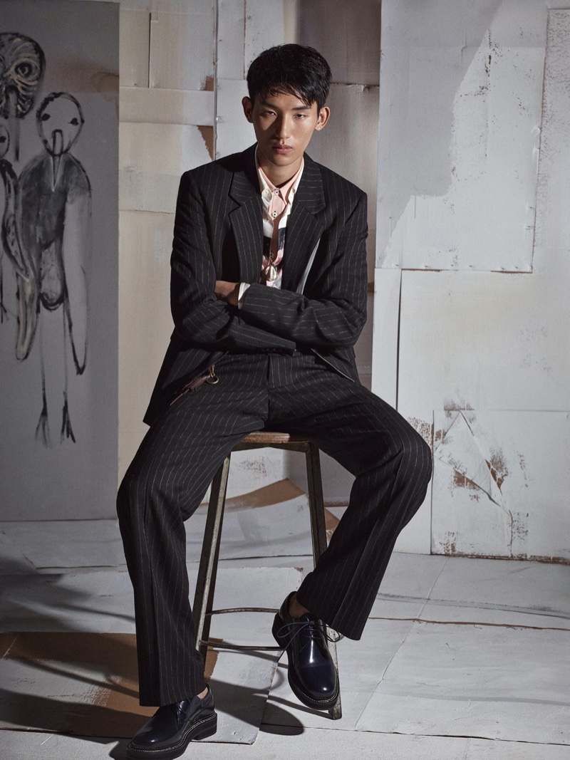 Jun Young Hwang dons a pinstripe suit with an abstract print shirt for Zara's fall-winter 2020 men's campaign.