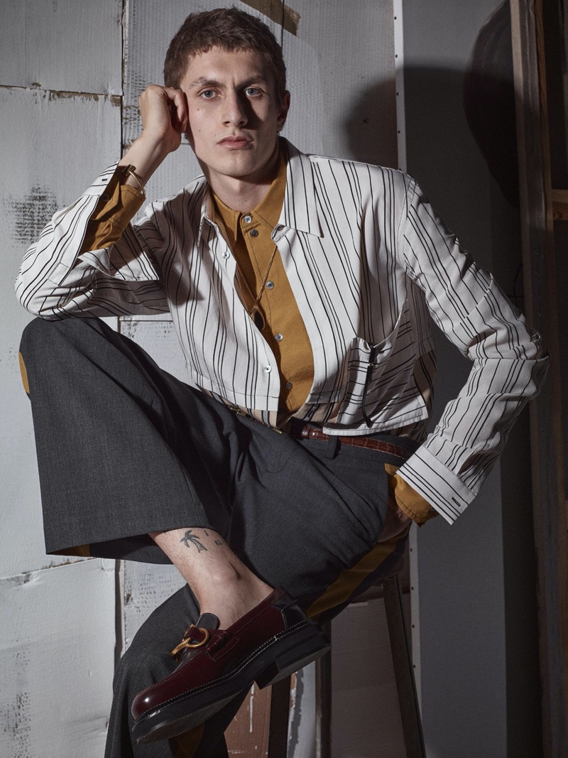 Henry Kitcher fronts Zara's fall-winter 2020 men's campaign. Sitting for a portrait, the top model wears a mixed stripe shirt over a button-down with trousers. A brown leather belt and loafers bring his look together.