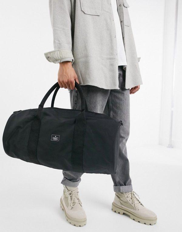 ASOS DESIGN gym barrel bag in black nylon with shoulder strap 37 litres