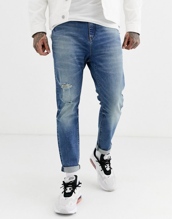 ASOS DESIGN tapered jeans in vintage mid wash blue with rips