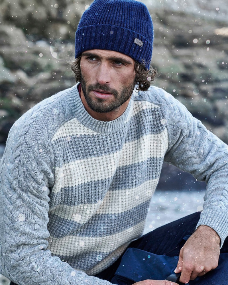 Model Alex Libby dons a striped cable-knit sweater from Barbour.