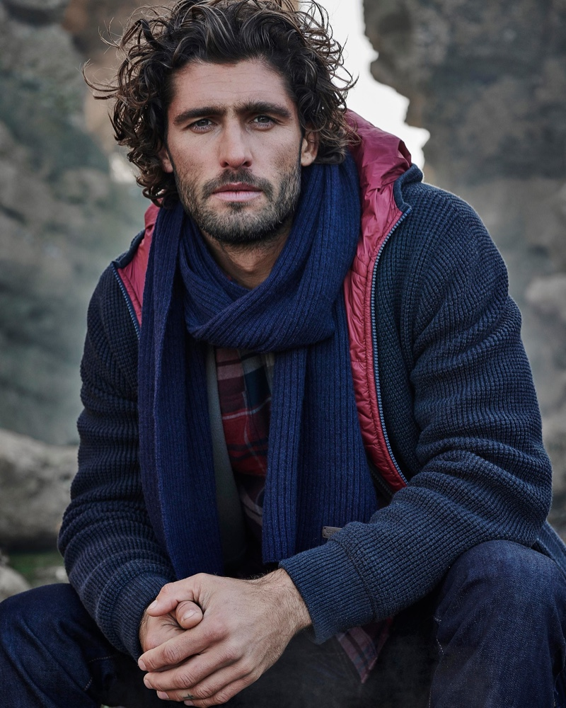 Layering in navy tones, Alex Libby wears a hooded knit jacket, scarf, and flannel shirt from Barbour.