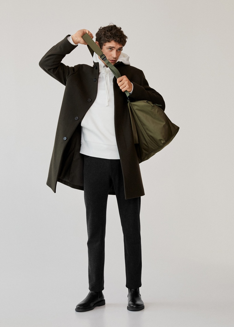 French model Arthur Gosse dons Mango Man's tailored wool-blend overcoat with a white hoodie and pants.