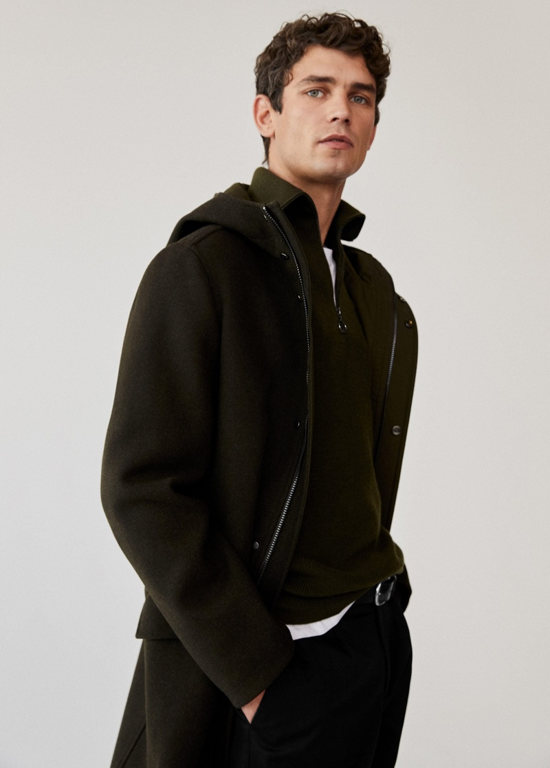 Arthur Gosse dons a long recycled wool coat with a zip neck sweater from Mango Man.
