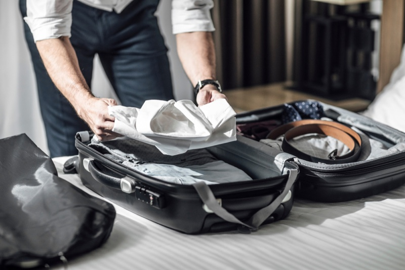 Businessman Packing Suitcase Bed
