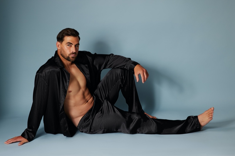 Model Marc Jacobs wears a black satin pajama set from Frederick's of Hollywood.