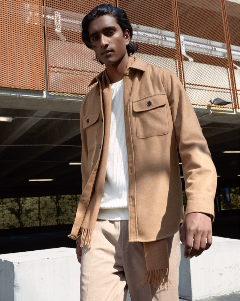 Model Jeenu Mahadevan rocks an on-trend twill shirt jacket over a ribbed sweater by H&M.