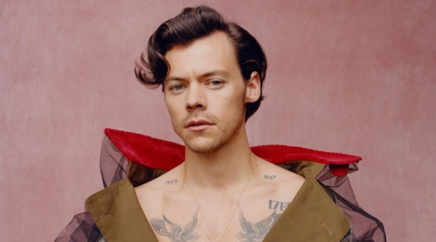 Front and center, Harry Styles wears a trench coat by Maison Margiela for Vogue.