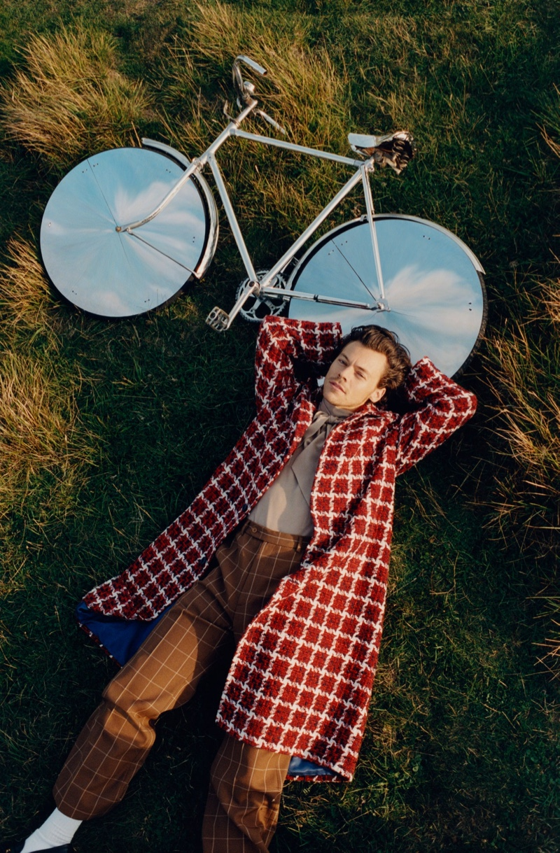 Laying in the grass, Harry Styles wears a Gucci overcoat with a shirt and pants for Vogue.