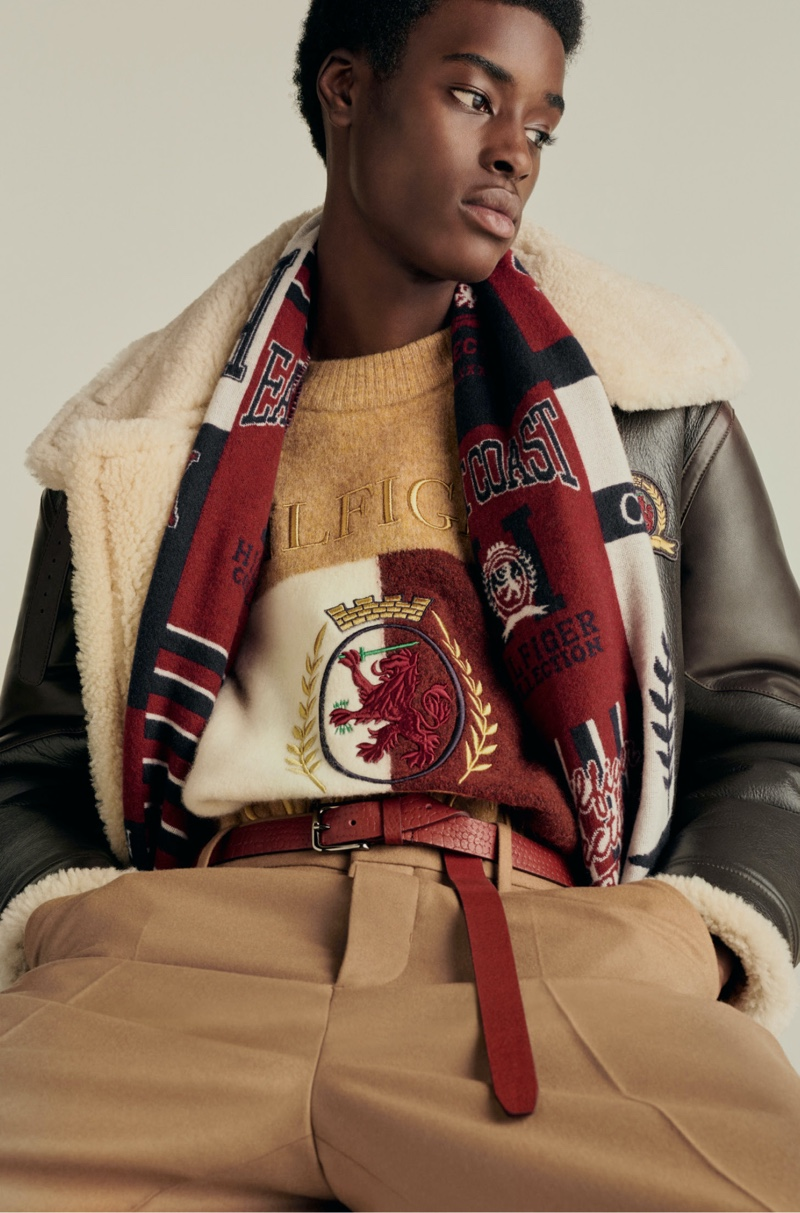 Babacar N'doye wears a shearling aviator jacket with a crest and flag sweater and relaxed pants from Hilfiger Collection.