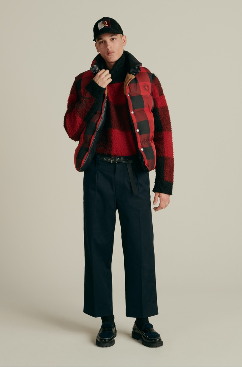 Front and center, Marco Pickett models a Hilfiger Collection suede cap, reversible Re:Down vest, buffalo check turtleneck sweater, relaxed pleated chinos, and skinny rock belt.