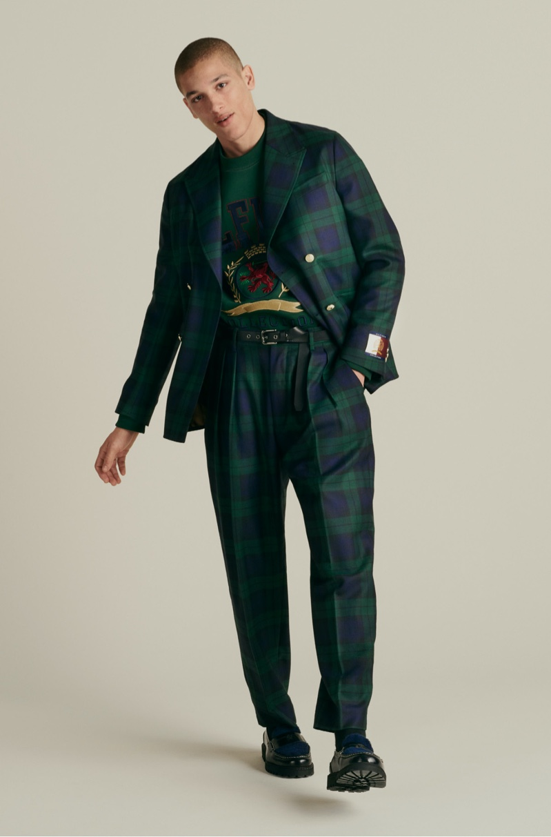 Going sartorial, Marco Pickett wears a Hilfiger Collection boxy check blazer and tapered pants with a bonded fringe logo sweatshirt, and skinny rock belt.