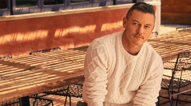 Actor Luke Evans sports a Todd Snyder cable fisherman's sweater in off white with cream and black houndstooth wool pleated pants.