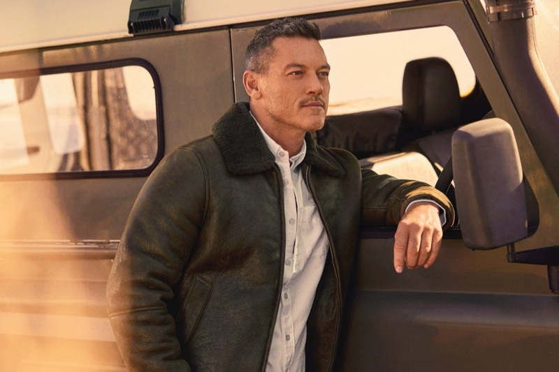 Sporting Todd Snyder's shearling aviator jacket in olive, Luke Evans also wears the brand's solid oxford shirt in white.