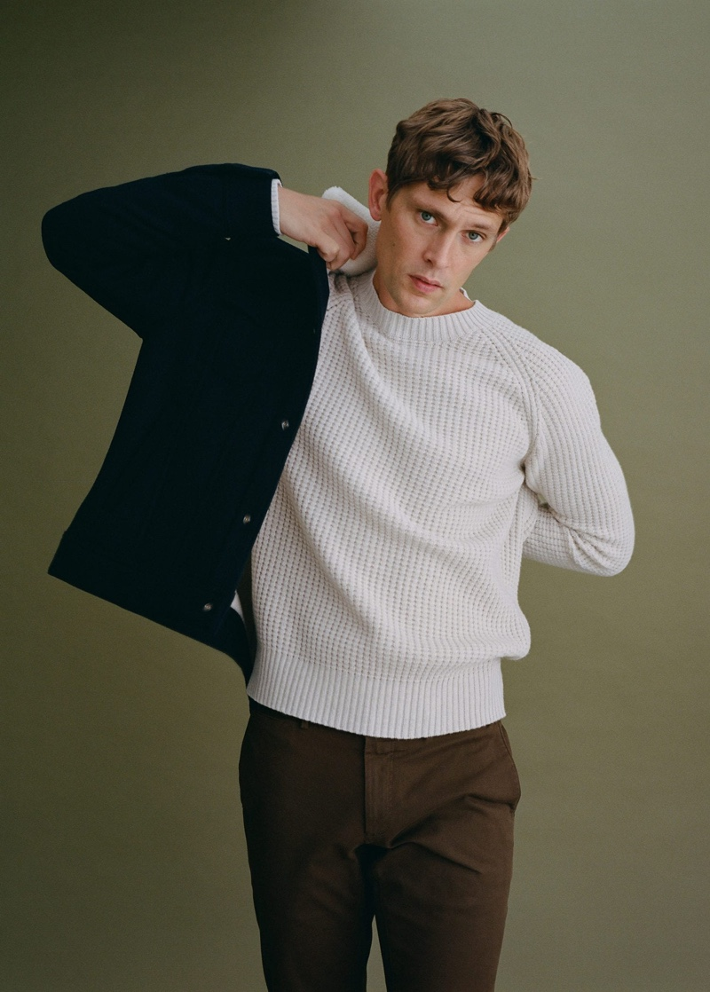 Front and center, Mathias Lauridsen dons a knit sweater, trousers, and a warm jacket from Mango.