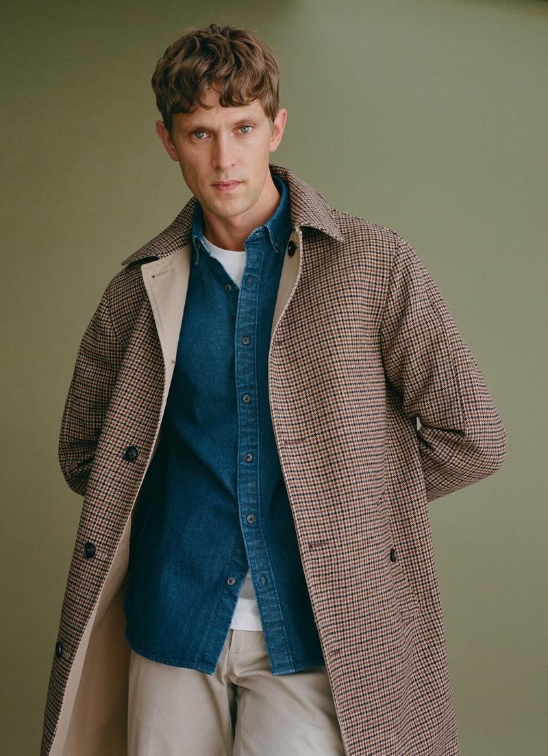 Donning a check coat and denim shirt, Mathias Lauridsen wears Mango.