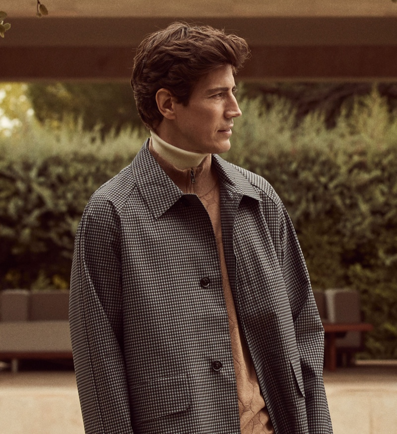 Spanish model Oriol Elcacho wears a houndstooth coat with a layered turtleneck sweater and zippered collar sweater.