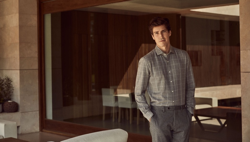 Model Oriol Elcacho dons a grey check shirt with pleated trousers from Pedro del Hierro.