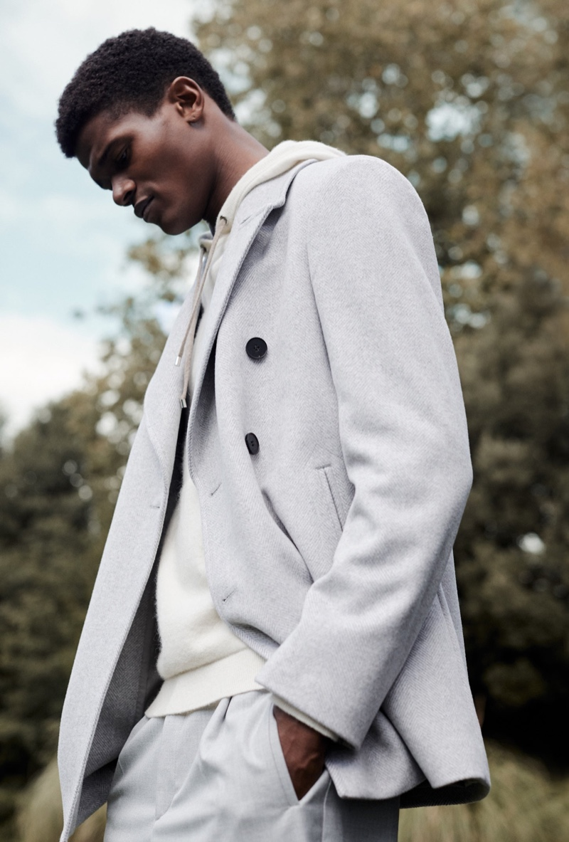 Delivering a side profile, O'Shea Robertson models a double-breasted coat with a hoodie and trousers for Reiss' fall-winter 2020 campaign.
