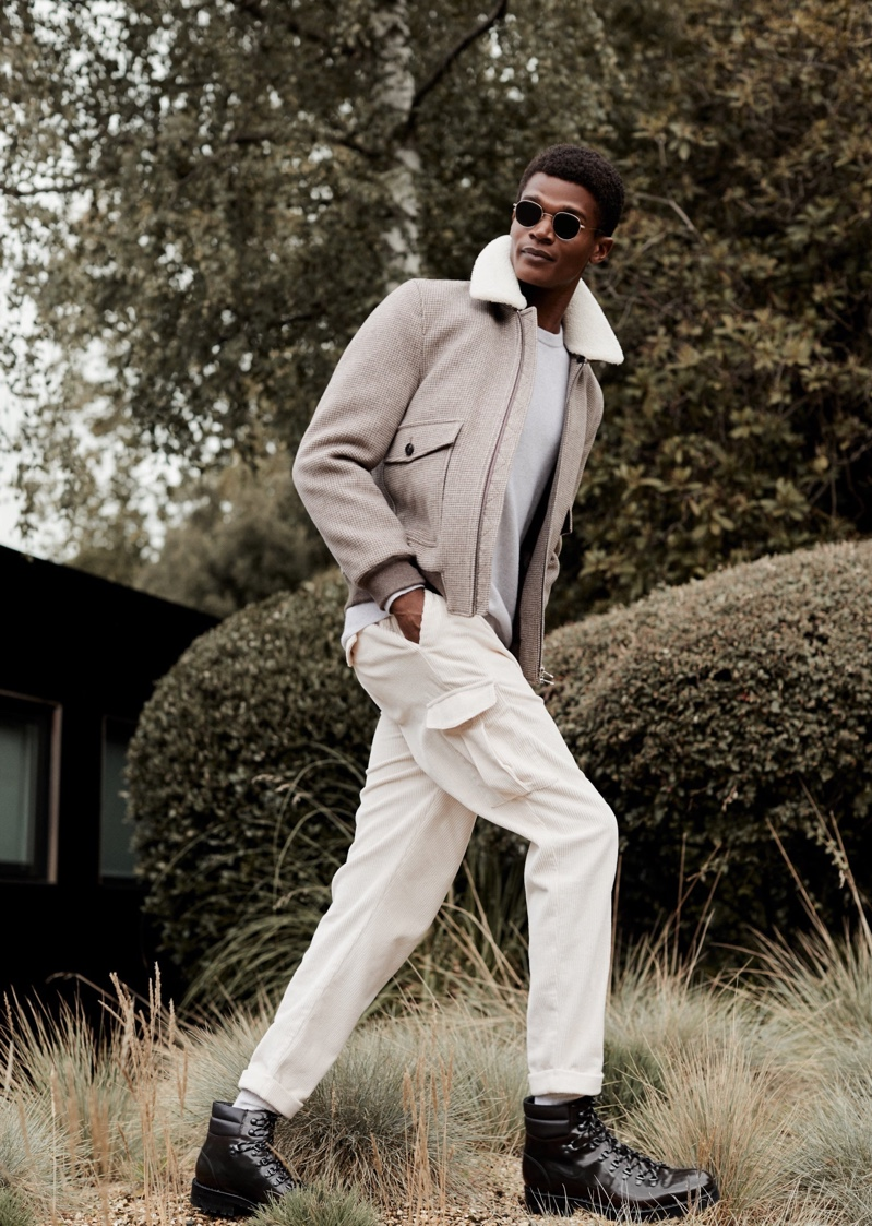 A sleek vision, O'Shea Robertson dons a jacket, sweater, and cargo trousers for Reiss' winter 2020 campaign.