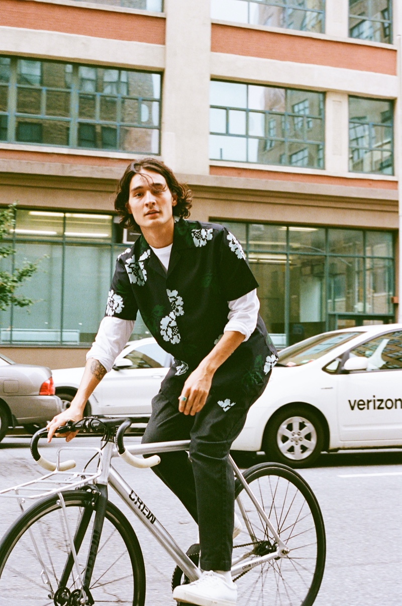 Riding a bike, Sebastião Hungerbühler wears Saturdays New York City's Canty Rose shirt with its Dean trousers.