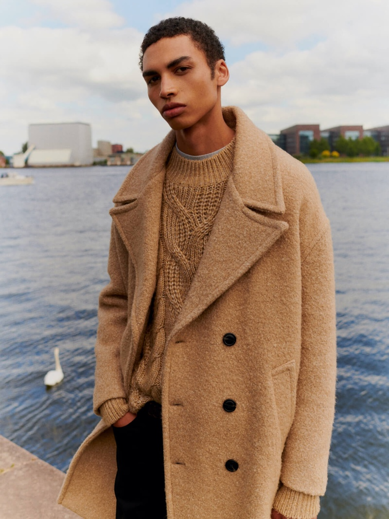 Sol Goss dons a chic winter coat with a cable-knit sweater from Scotch & Soda.